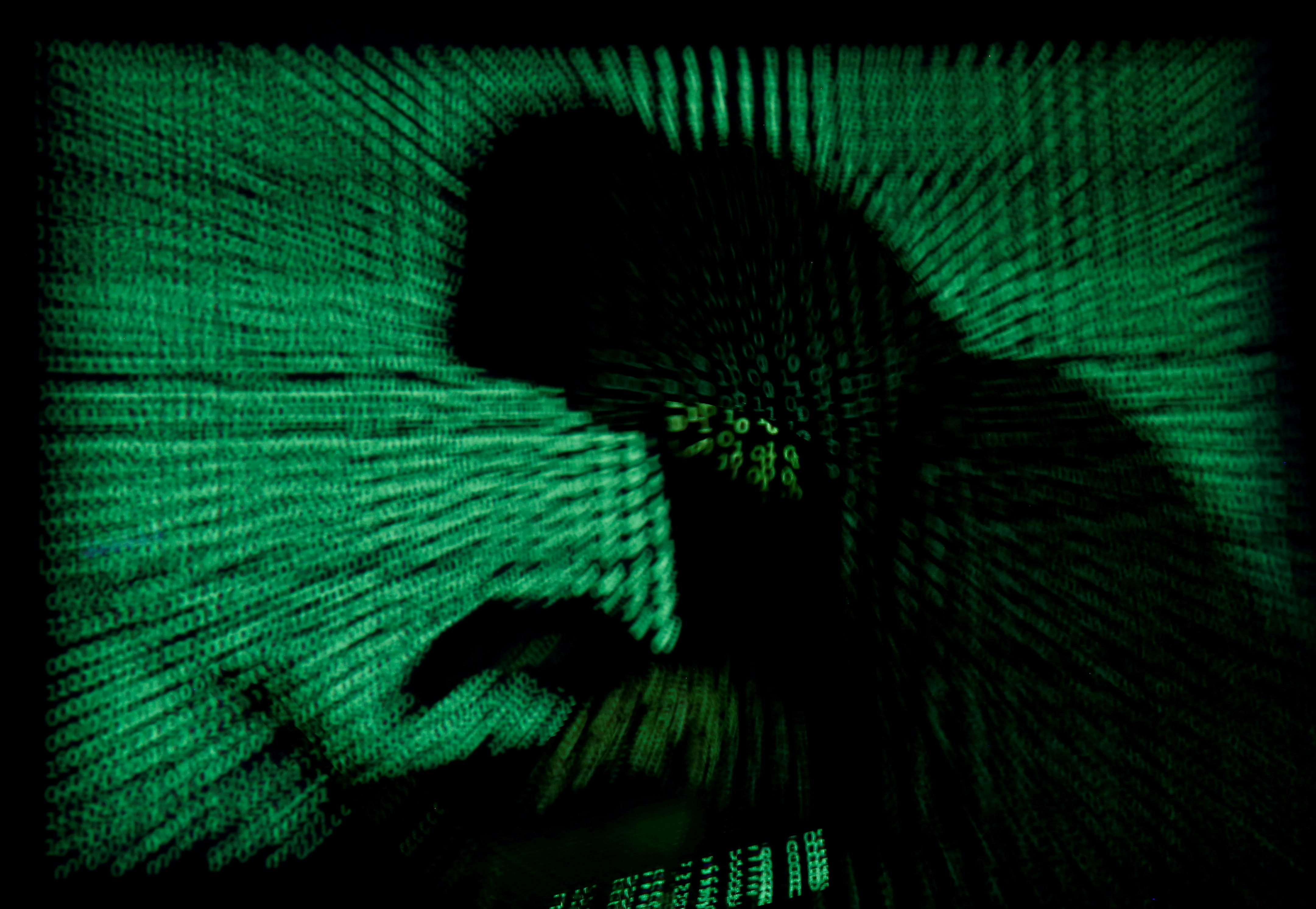 A hooded man holds a laptop computer as cyber code is projected on him in this illustration picture taken on May 13, 2017.  REUTERS/Kacper Pempel/Illustration/File Photo