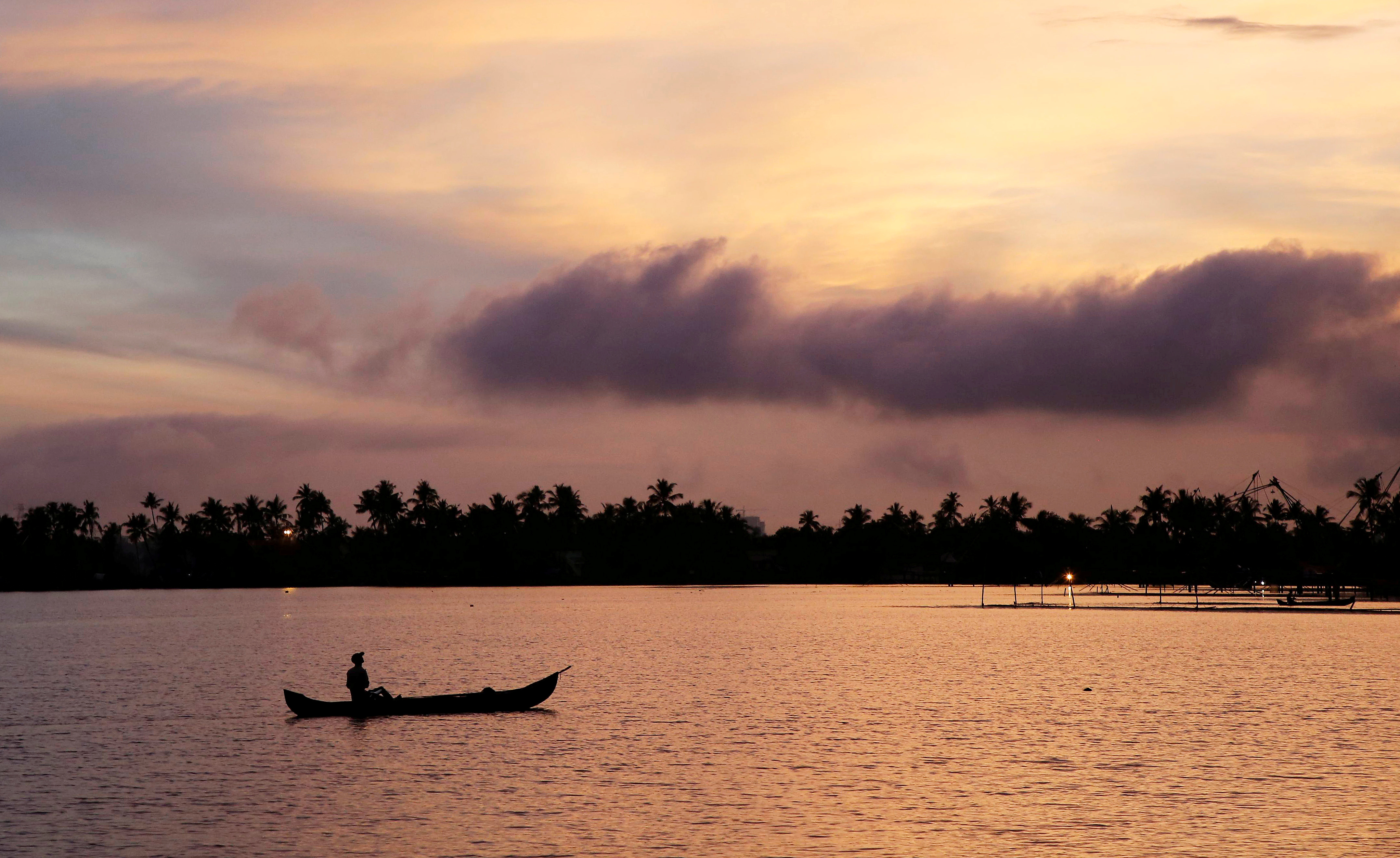 A man rows his boat in the tributary waters of Vembanad Lake against the backdrop of pre-monsoon clouds on the outskirts of Kochi, India, June 7, 2019. REUTERS/Sivaram V/File Photo