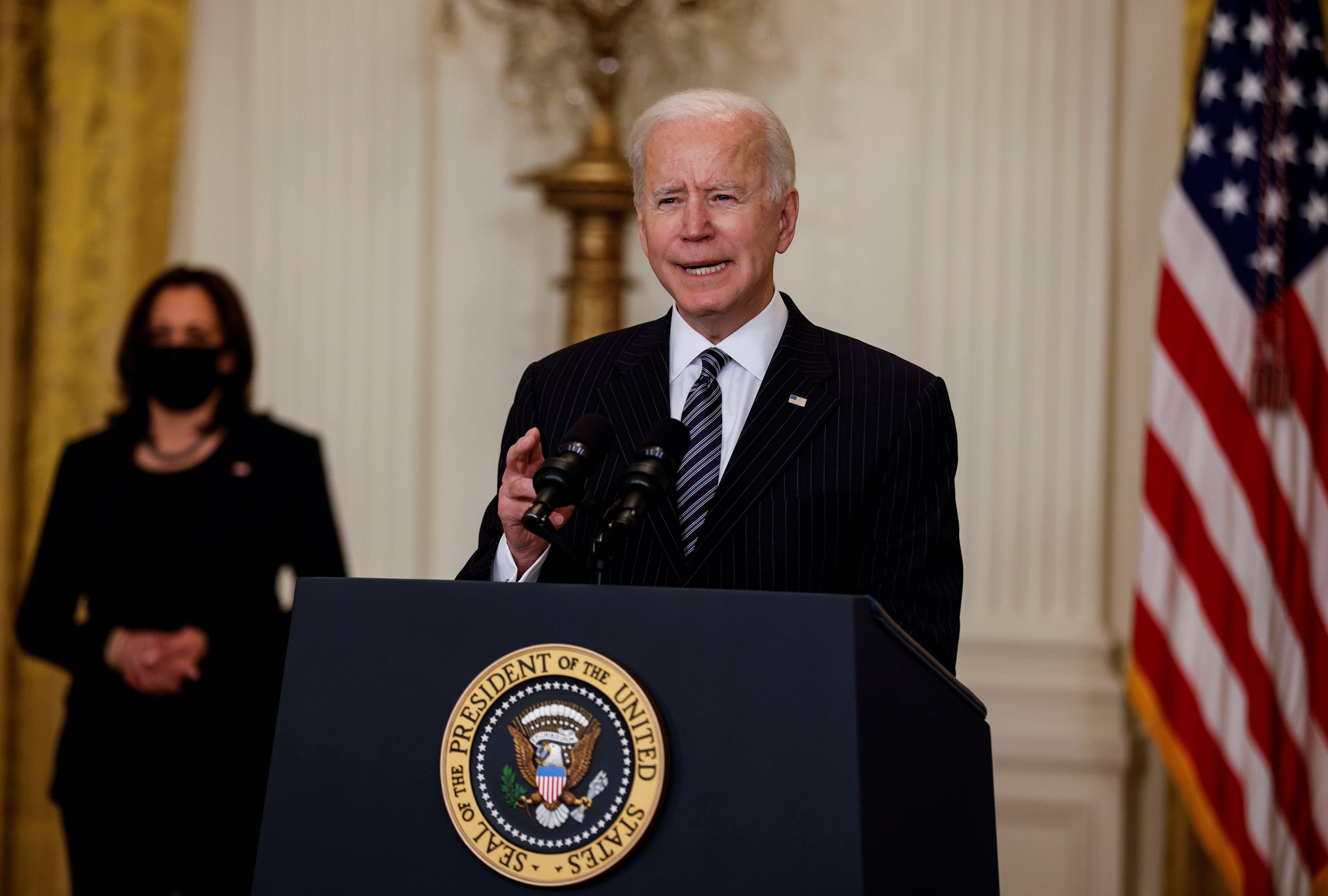 U.S. President Joe Biden speaks about the state of vaccinations as Vice President Kamala Harris listens during a coronavirus disease (COVID-19) response event in the East Room at the White House in Washington, U.S., March 18, 2021. REUTERS/Carlos Barria