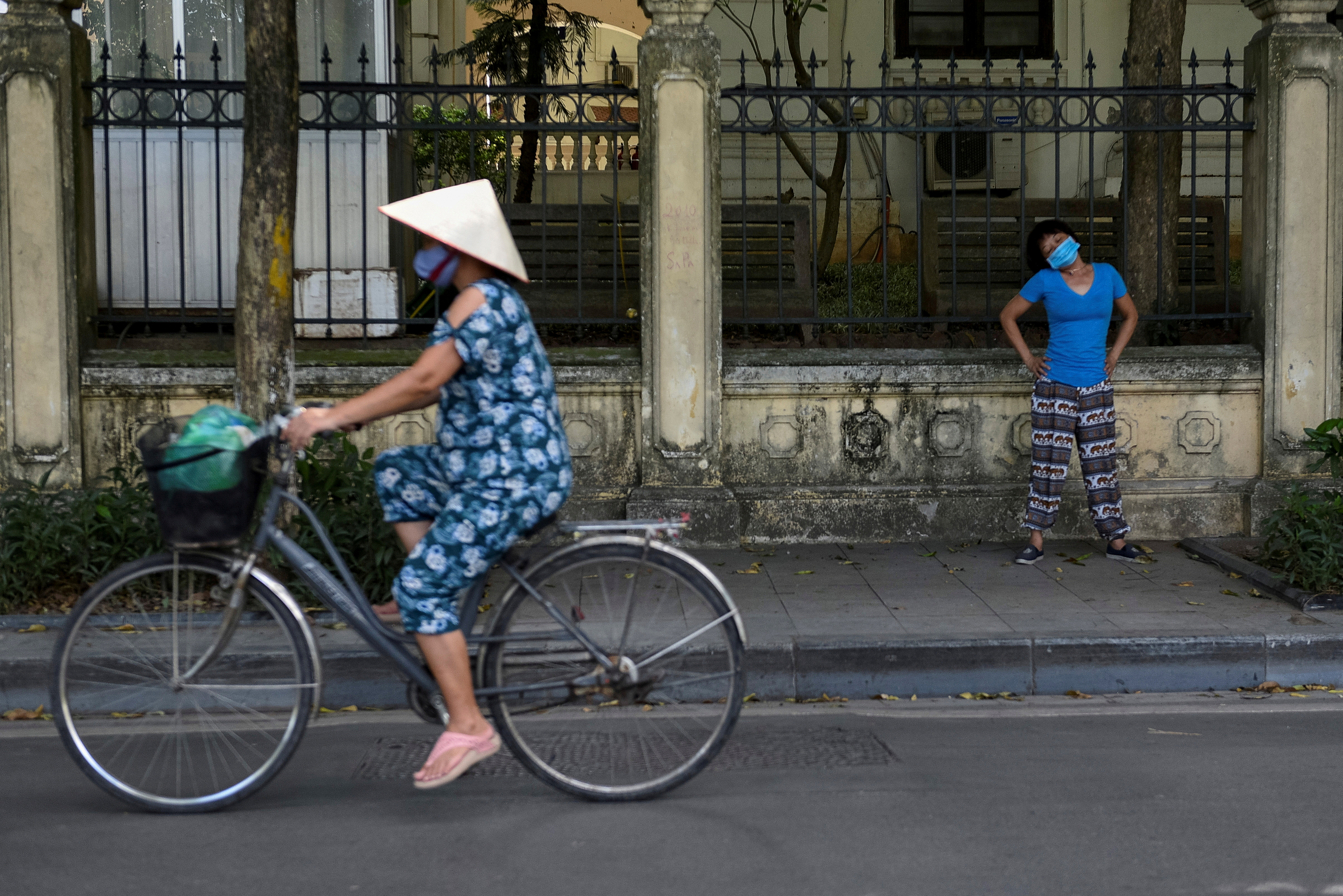 A woman wears a protective mask as she exercises on the street amid the coronavirus (COVID-19) pandemic, in Hanoi, Vietnam, May 31. REUTERS/Thanh Hue