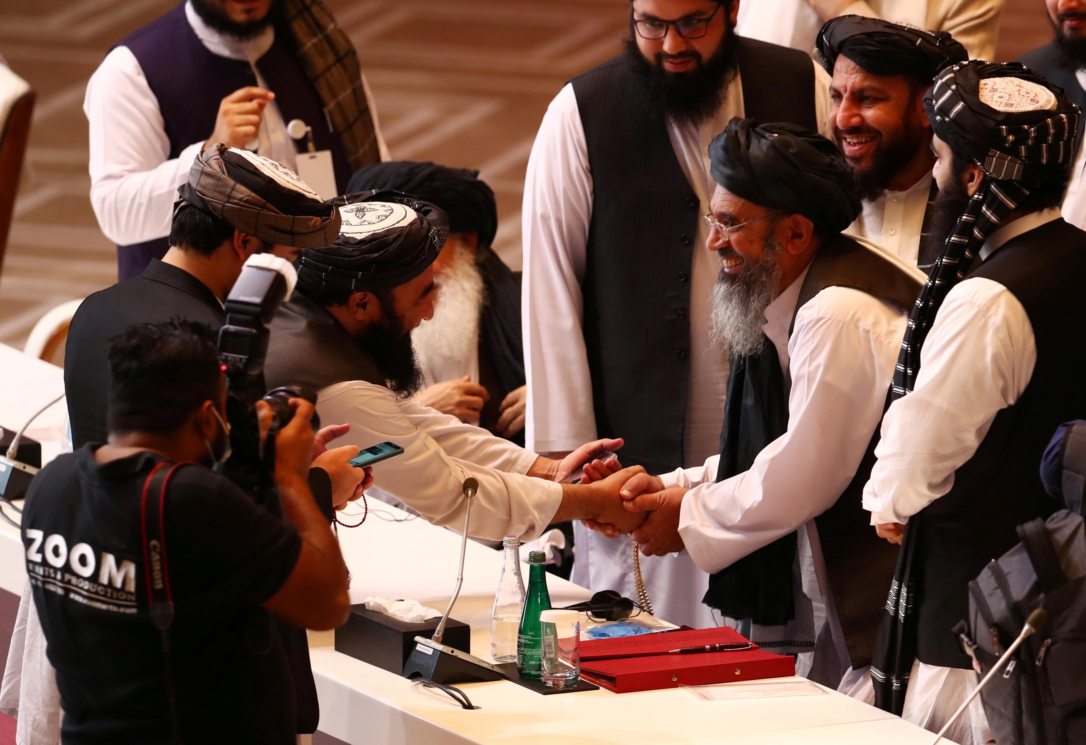 Taliban delegates shake hands during talks between the Afghan government and Taliban insurgents in Doha, Qatar September 12, 2020. REUTERS/Ibraheem al Omari/File Photo