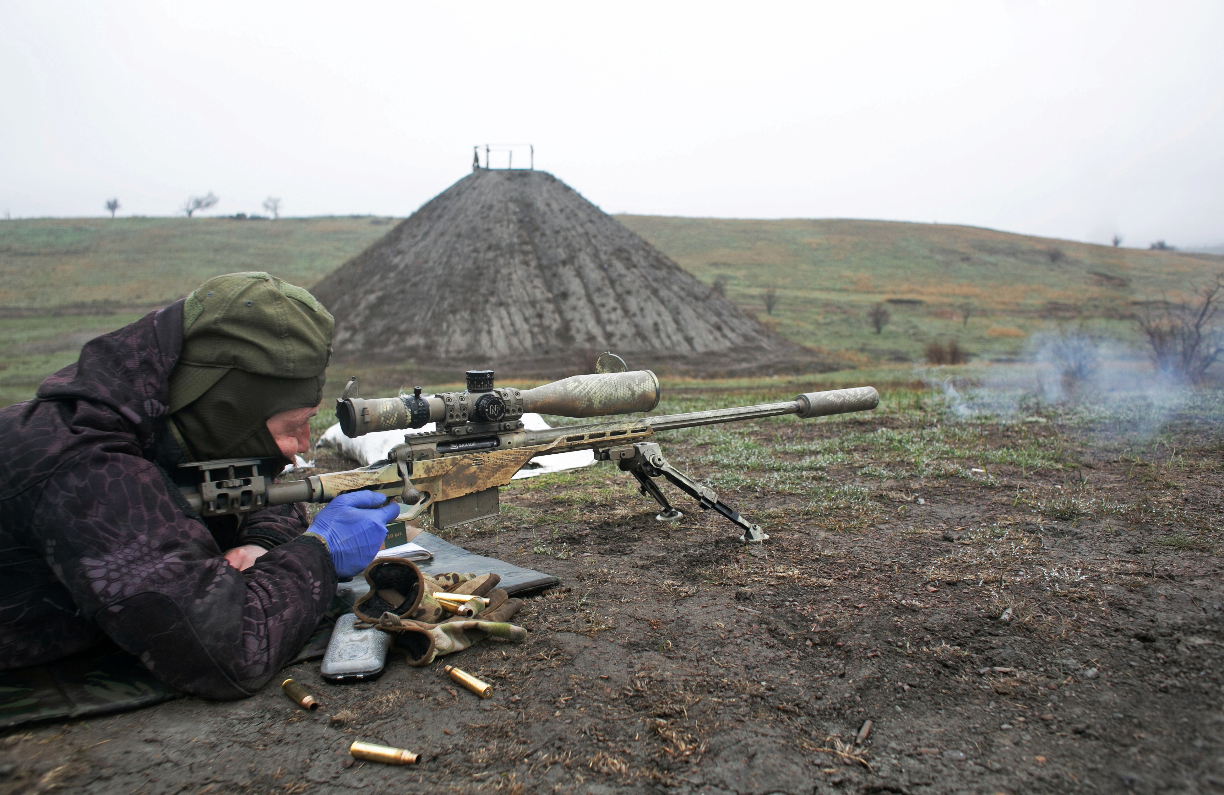 A sniper of the Ukrainian armed forces fires his rifle during training at a firing range near the town of Marinka inDonetsk region, Ukraine April 13, 2021. REUTERS/Anastasia Vlasova