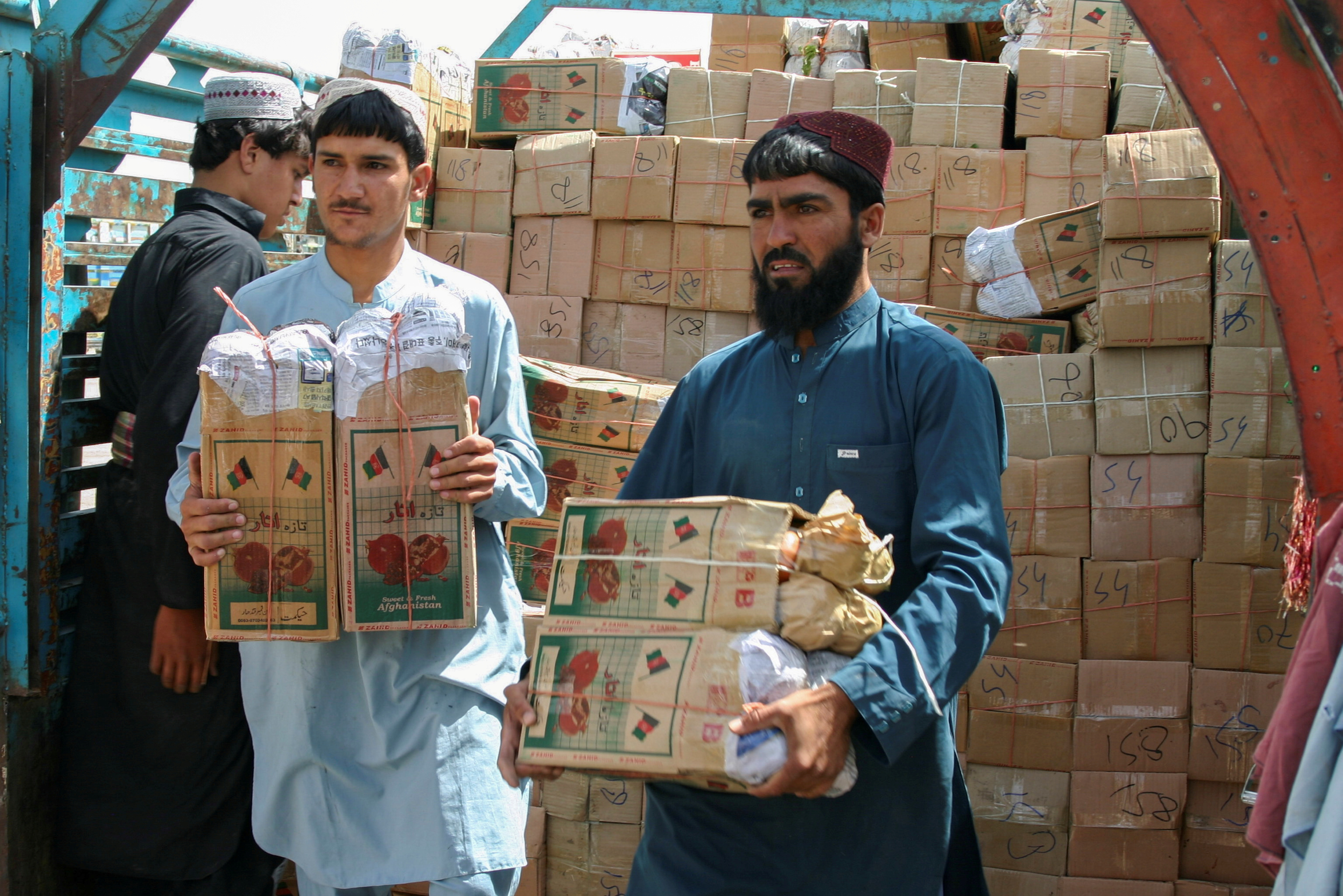 Labourers unload boxes of pomegranates from Afghanistan, from a truck at the 'Friendship Gate' crossing point, in the Pakistan-Afghanistan border town of Chaman, Pakistan, September 7, 2021. REUTERS/Saeed Ali Achakzai/File Photo