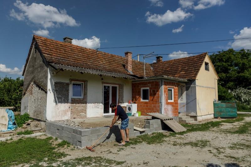 Danijel Harmnicar, owner of house bought for 1 HRK, works in yard in village Legrad, Croatia, June 10, 2021. REUTERS/Antonio Bronic