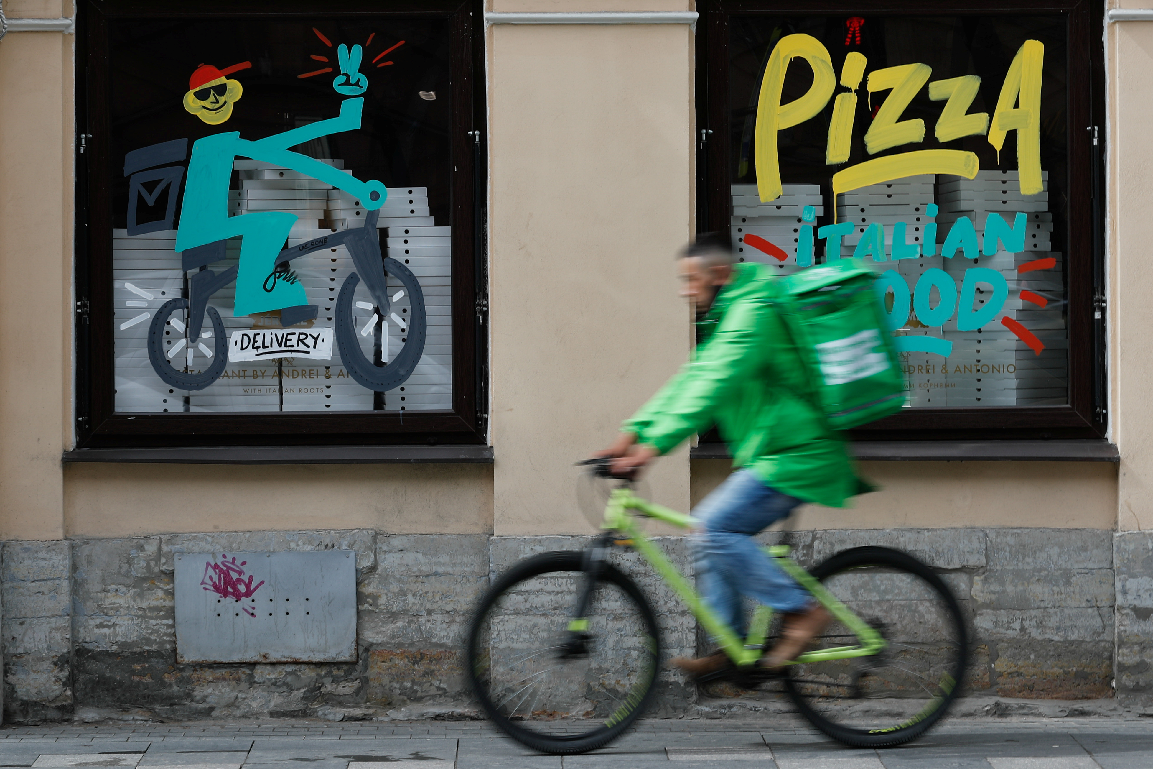 A courier of Delivery Club company rides a bicycle past a restaurant, amid the outbreak of the coronavirus disease (COVID-19) in Saint Petersburg, Russia June 5, 2020. REUTERS/Anton Vaganov