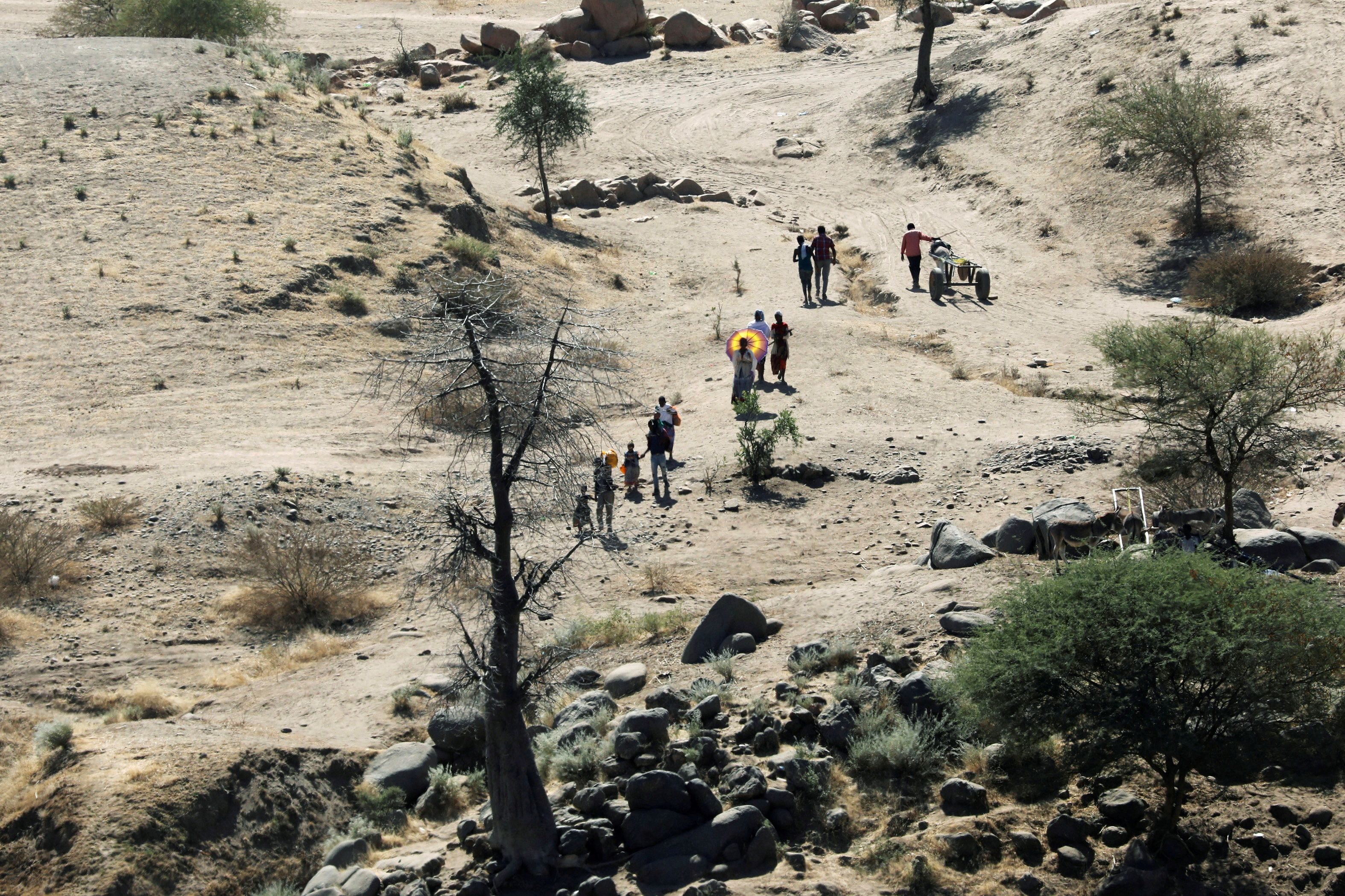 Ethiopians fleeing from the Tigray region walk towards a river to cross from Ethiopia to Sudan, near the Hamdeyat refugee transit camp, which houses refugees fleeing the fighting in the Tigray region, on the border in Sudan, December 1, 2020. REUTERS/Baz Ratner/File Photo