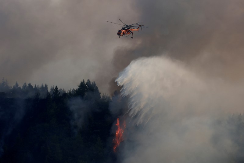 A firefighting helicopter makes a water drop as a wildfire burns in the village of Galatsona, on the island of Evia, Greece, August 10, 2021. REUTERS/Nicolas Economou