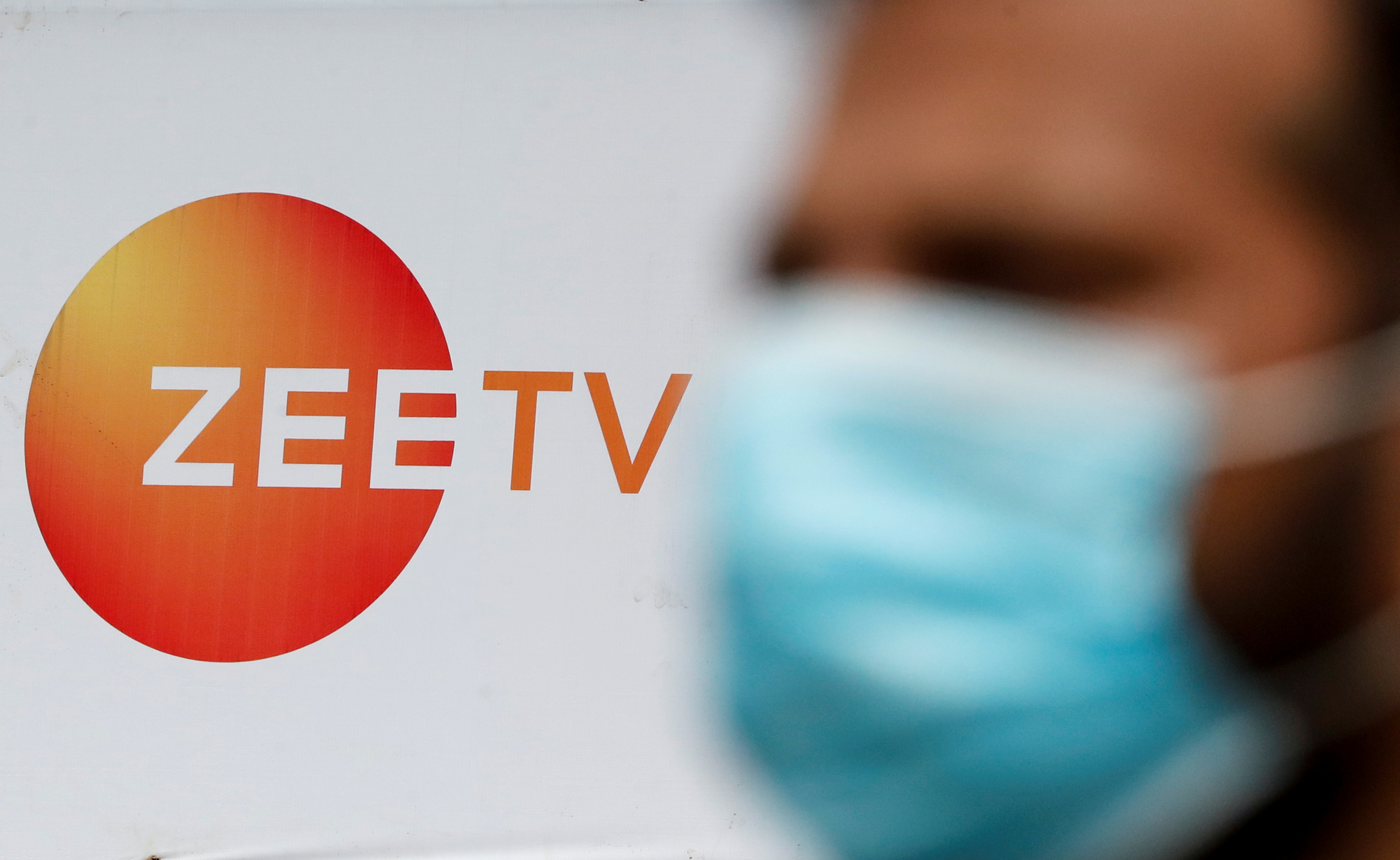 A guard stands next to a banner of Zee television outside a film studio in Mumbai, India, September 24, 2021. REUTERS/Francis Mascarenhas - RC26WP9MQGQC