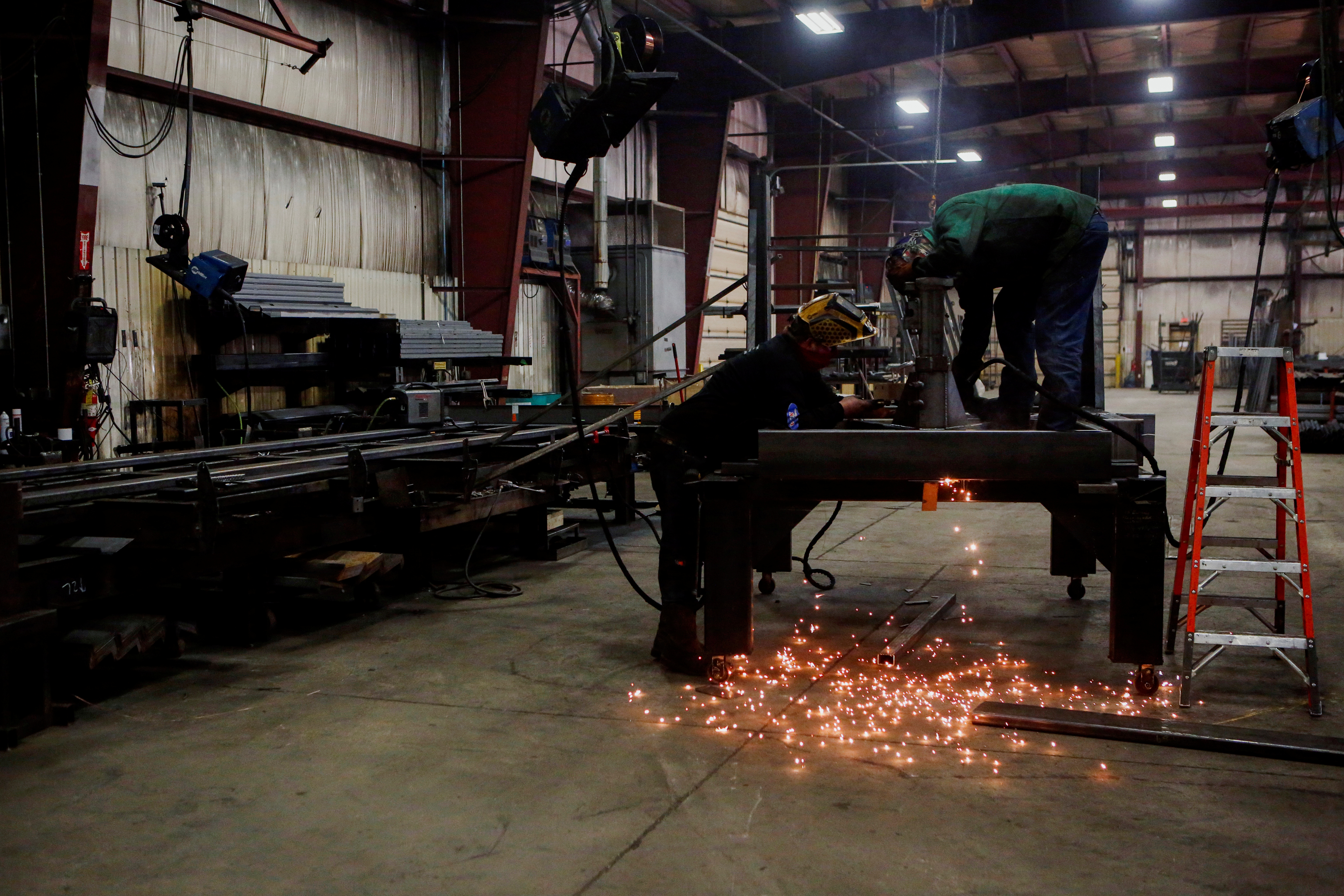 Matt Dillion and Chad Damron weld an upper deck assembly at Look Trailers cargo trailer manufacturing facility in Middlebury, Indiana, U.S., April 1, 2021. REUTERS/Eileen T. Meslar