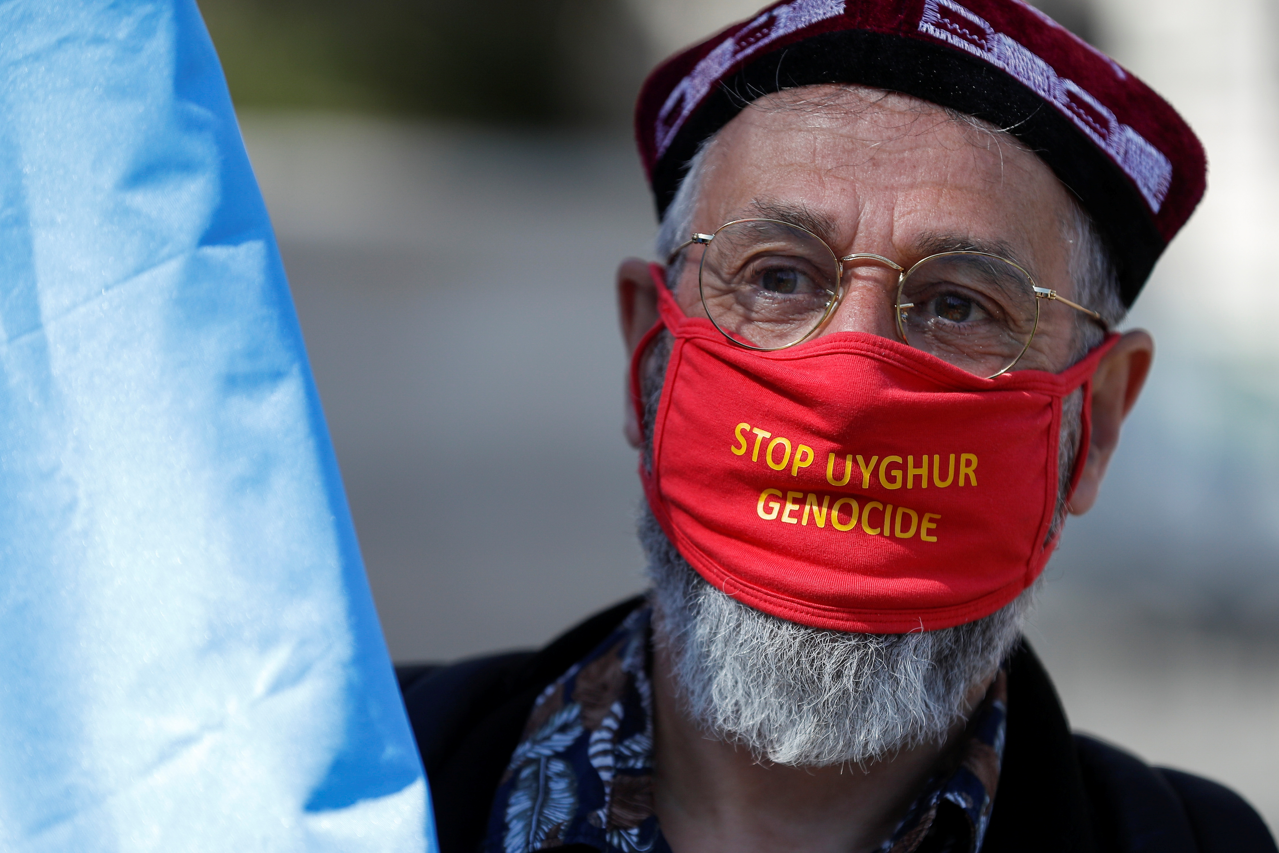 A demonstrator wears a face mask as he attends a protest against Uyghur genocide, in London, Britain April 22, 2021. REUTERS/Peter Nicholls