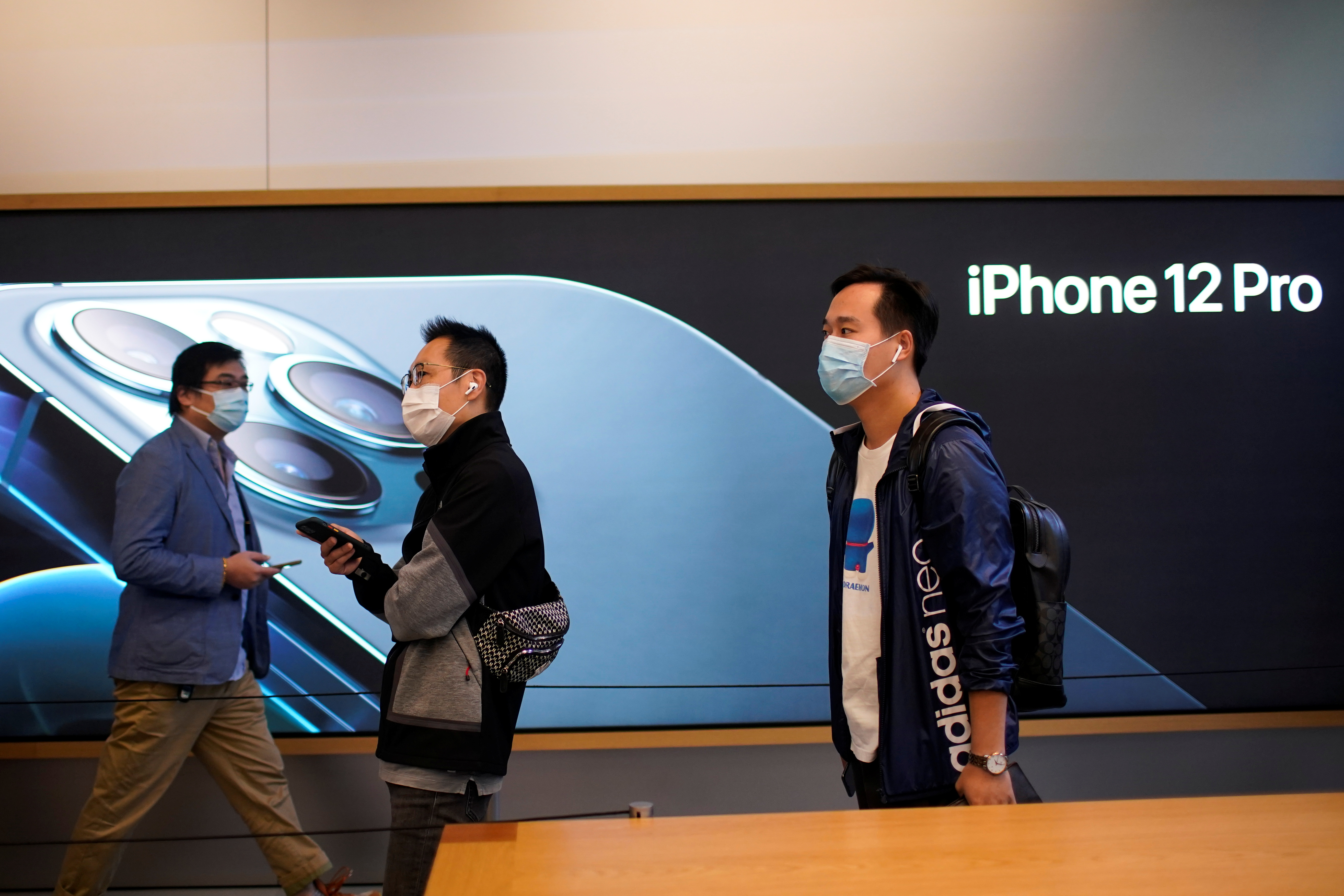 People wearing face masks wait at an Apple Store before Apple's 5G new iPhone 12 go on sale, as the coronavirus disease (COVID-19) outbreak continues in Shanghai China October 23, 2020. REUTERS/Aly Song