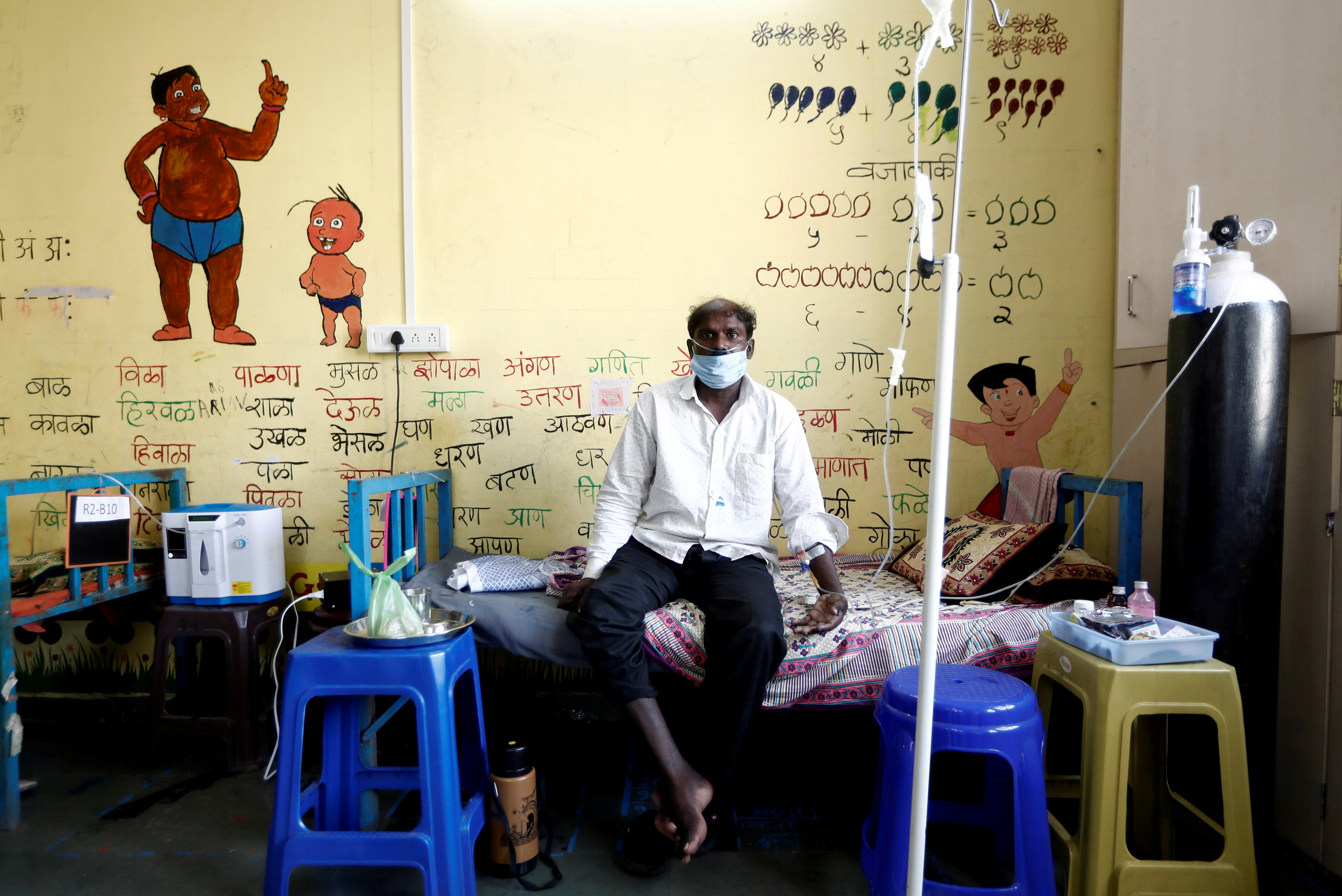 A man suffering from coronavirus disease (COVID-19) receives oxygen support as he sits inside the classroom of a school turned into a COVID-19 care facility on the outskirts of Mumbai, India, May 24, 2021. REUTERS/Francis Mascarenhas