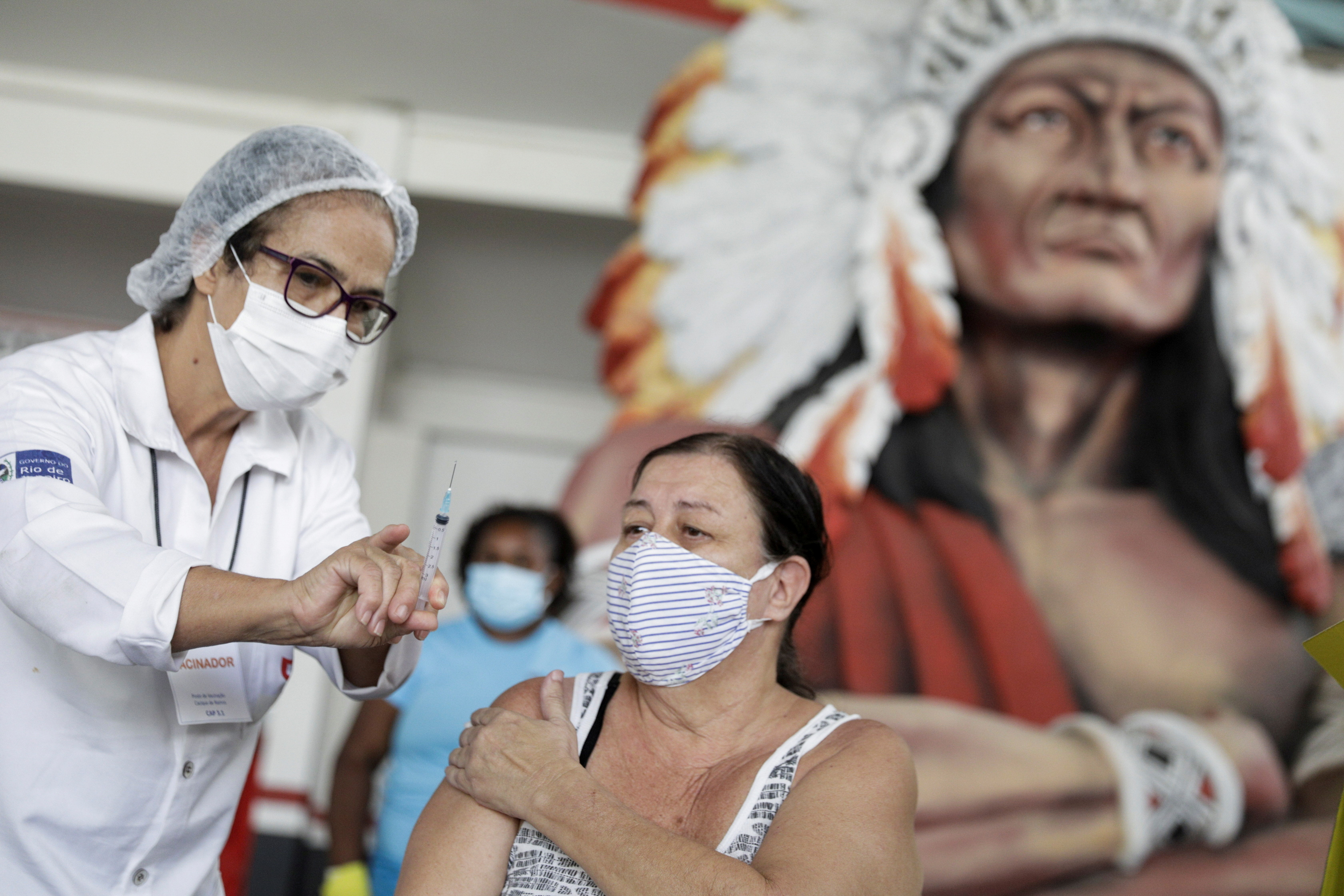 A healthcare worker shows the syringe to a woman after applying a dose of Sinovac's CoronaVac coronavirus disease (COVID-19) vaccine at Cacique de Ramos, one of the most traditional carnival blocks of Rio de Janeiro, Brazil April 8, 2021. REUTERS/Ricardo Moraes
