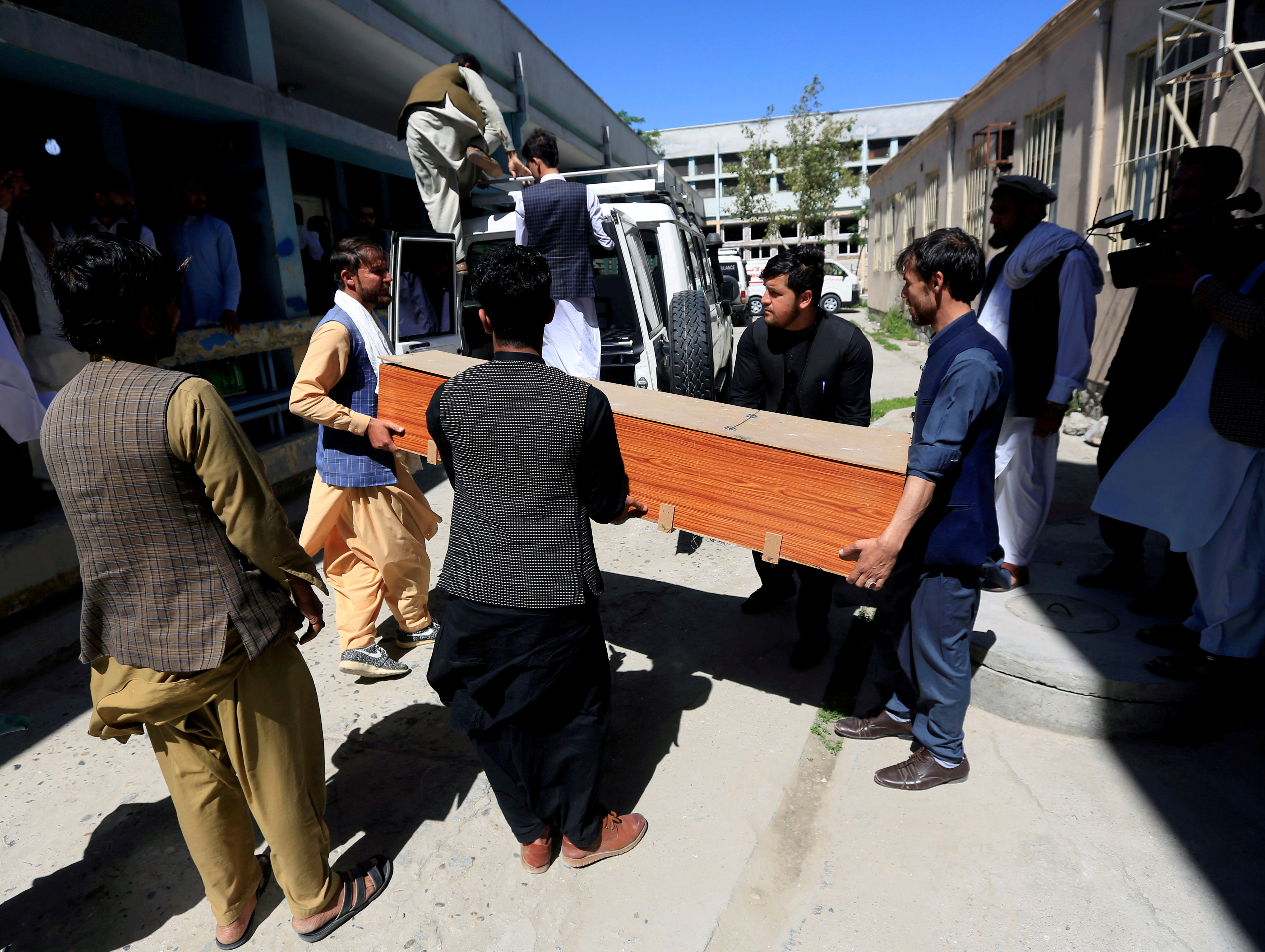 Afghan men carry the coffin of one of the three female polio vaccination health workers who were shot and killed by unknown gunmen at two separate locations, in Jalalabad, Afghanistan, March 30, 2021. REUTERS/Parwiz/File Photo