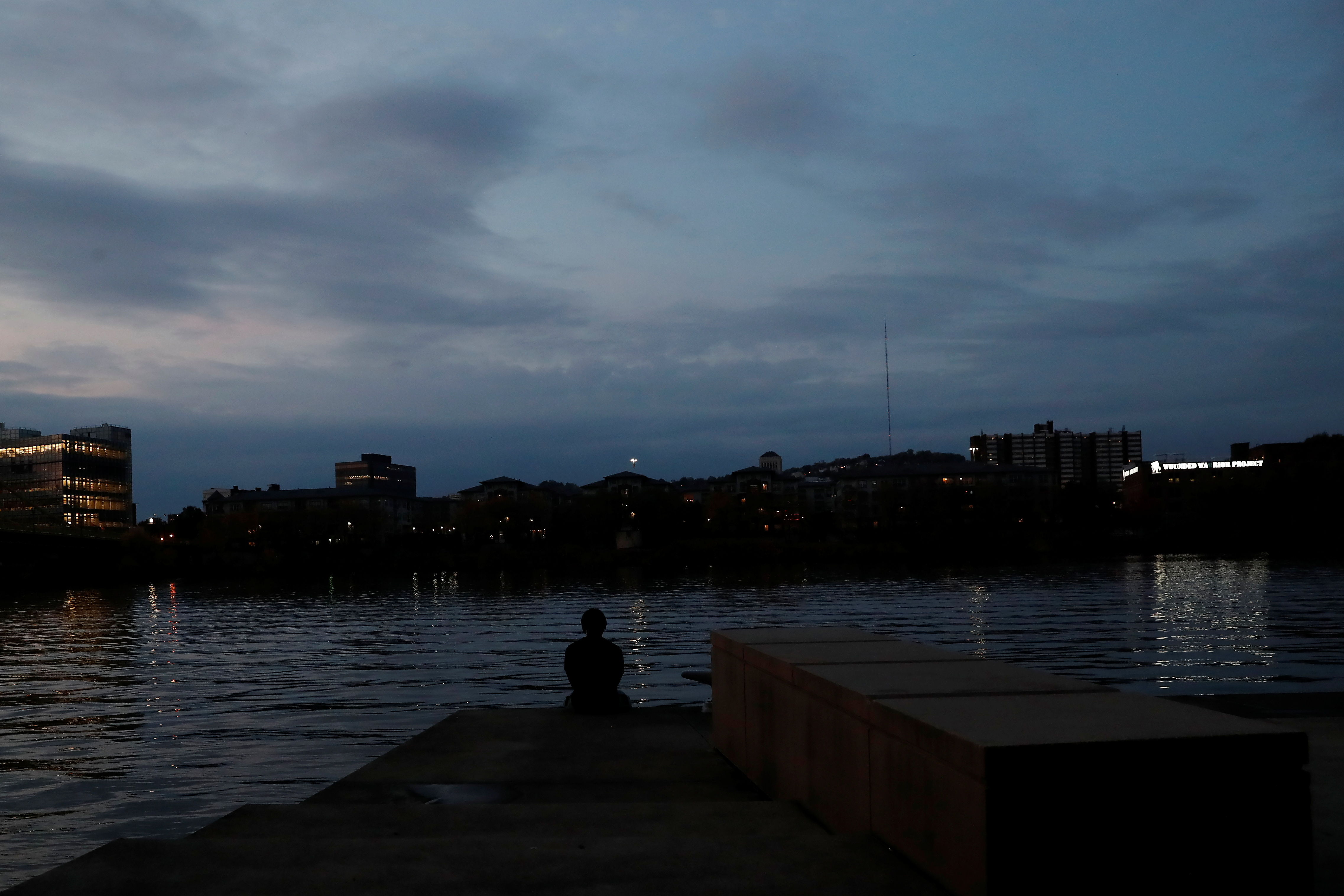 A man is silhouetted as he sits along the Allegheny River in Pittsburgh, Pennsylvania, U.S., October 21, 2020.  REUTERS/Shannon Stapleton