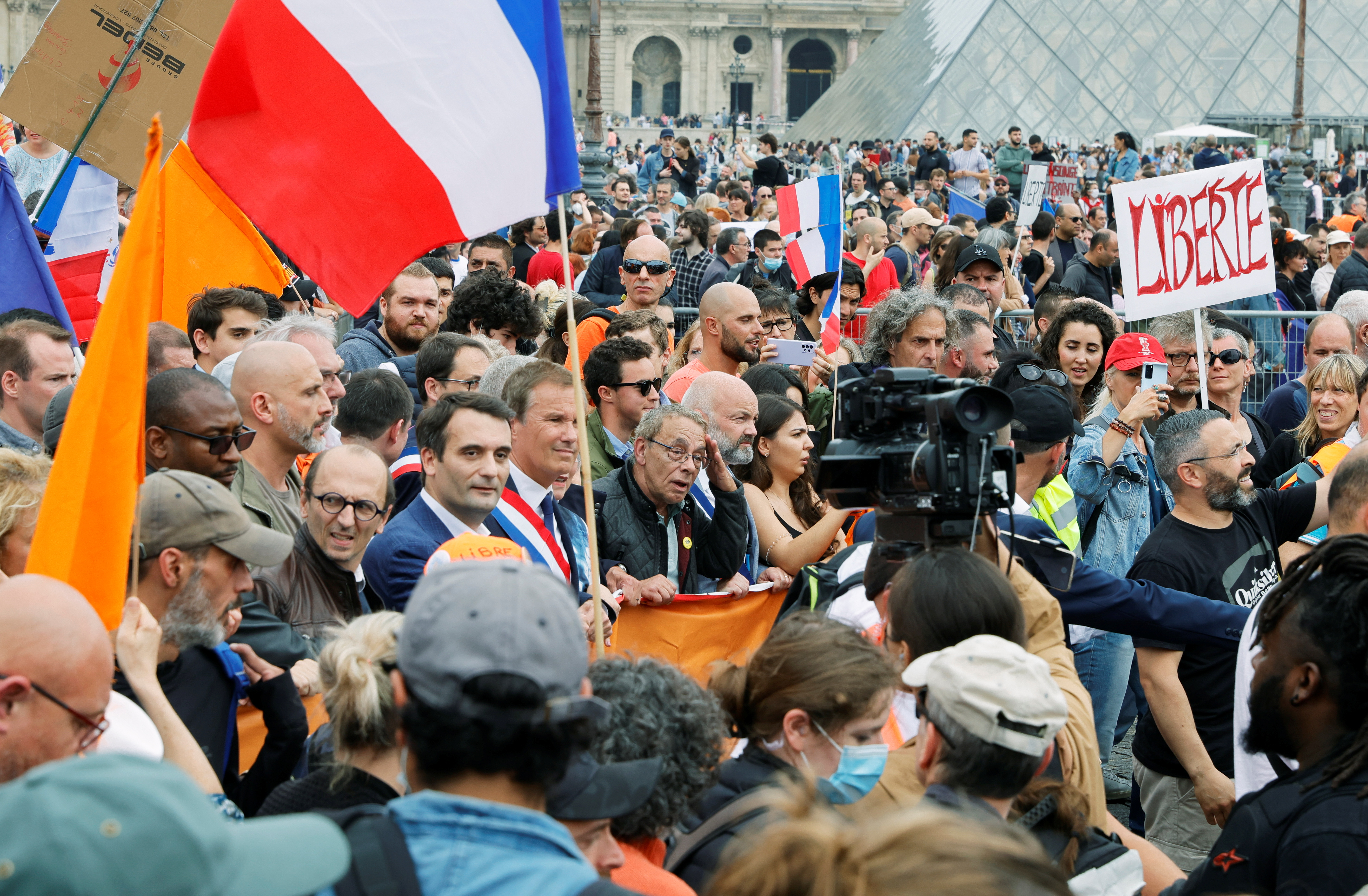 Florian Philippot, President of French political party Les Patriotes, and Nicolas Dupont-Aignan, head of French political party Debout La France (DLF) attend a protest against the new measures announced by French President Emmanuel Macron to fight the coronavirus disease (COVID-19) outbreak, in Paris, France, July 17, 2021. REUTERS/Pascal Rossignol