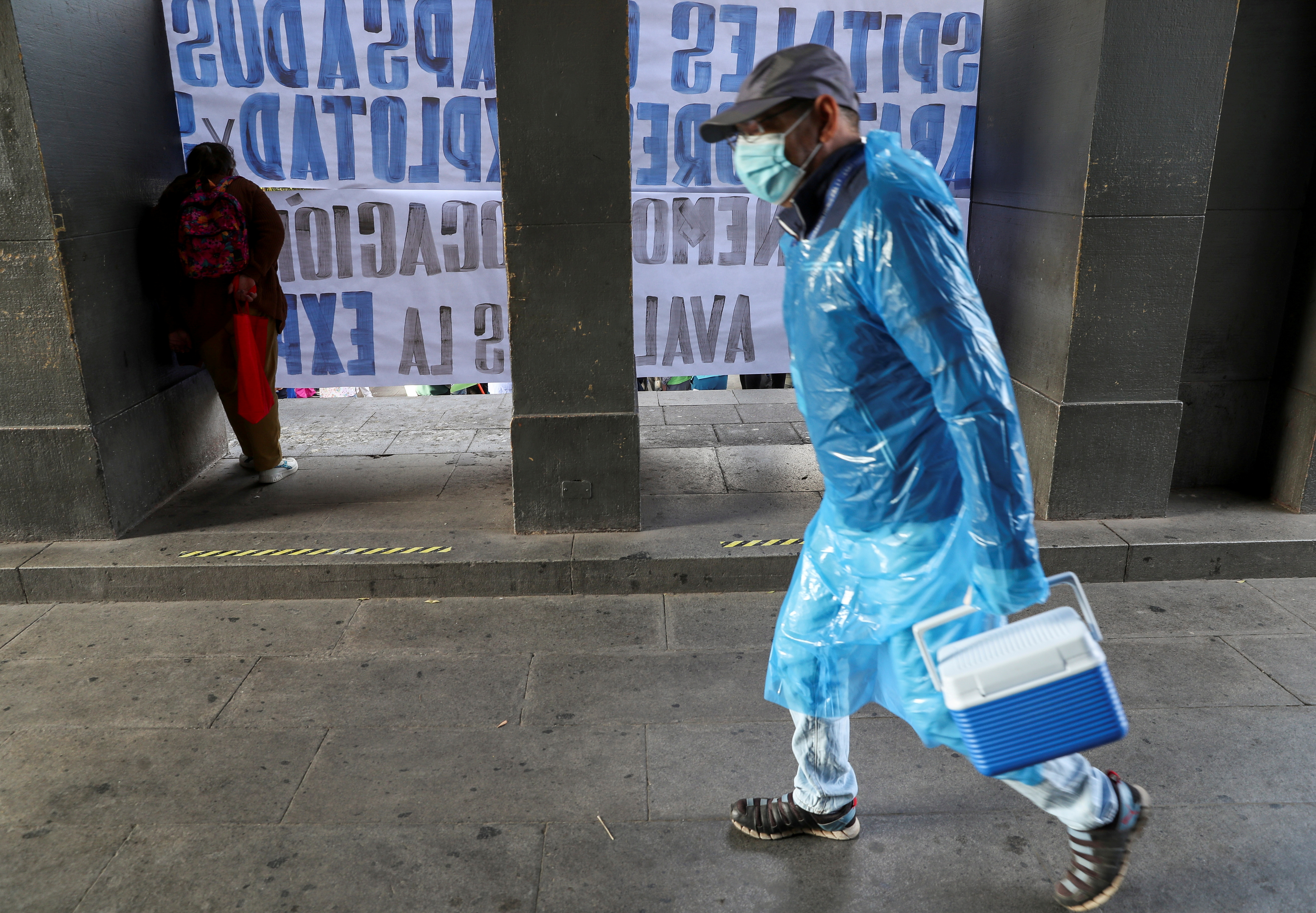 A healthcare worker carries a cooler during a rally outside a hospital to demand better work conditions, according to organisers, amid the coronavirus disease (COVID-19) pandemic in Santiago, Chile April 8, 2021. REUTERS/Ivan Alvarado/File Photo
